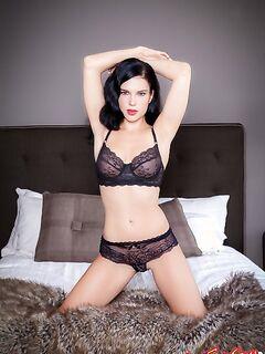 Красивая брюнетка сексуально позирует на кроватке фото
