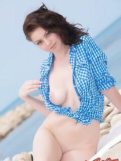 Голая девушка на берегу моря раздевается фото