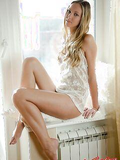 Красивая голая девушка позирует в окне фото