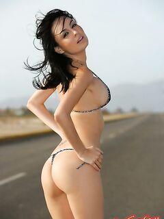 Красивая девушка в бикини стоит на дороге фото