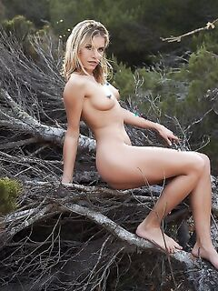 Симпатичная голая девка позирует на природе фото