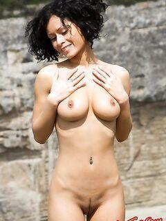 Грудастая секси девушка голой позирует на природе фото